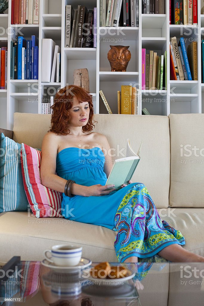 Girl sitting on coach reading book royalty-free stock photo