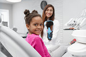 Little african girl sitting on dentist chair looking at camera and smiling while female dentist keeping mirror at backround. Child visiting dentist and enjoying smile after dental procedures.