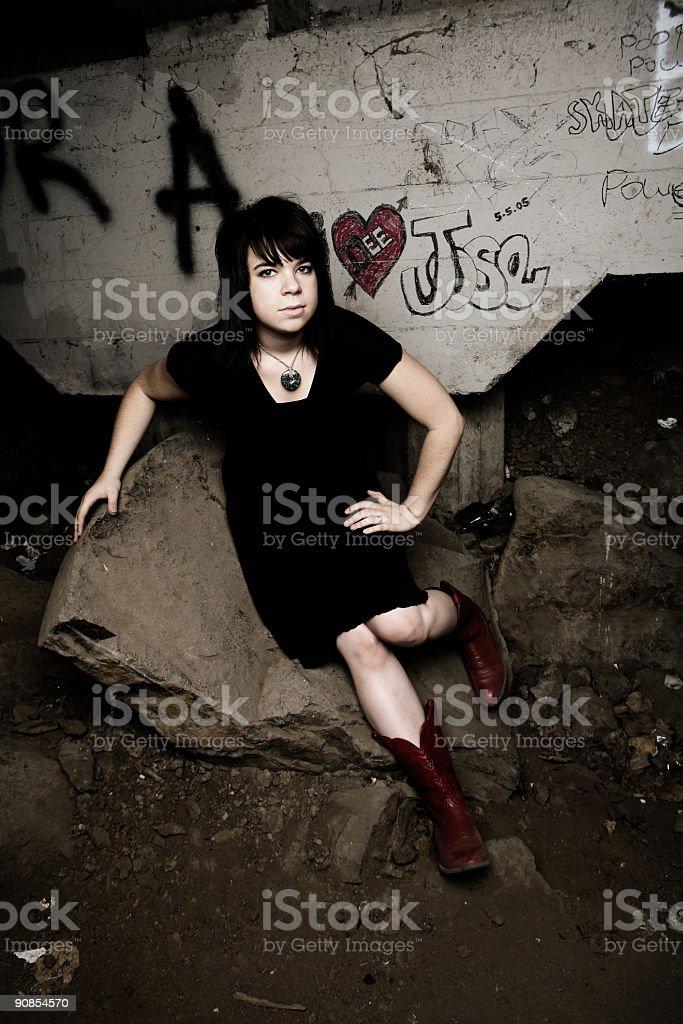 Girl Sitting on Dirty Rocks Under a Bridge stock photo