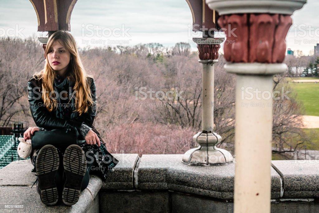 Girl sitting on edge of Belvedere Castle at Central Park in Manhattan, New York City stock photo