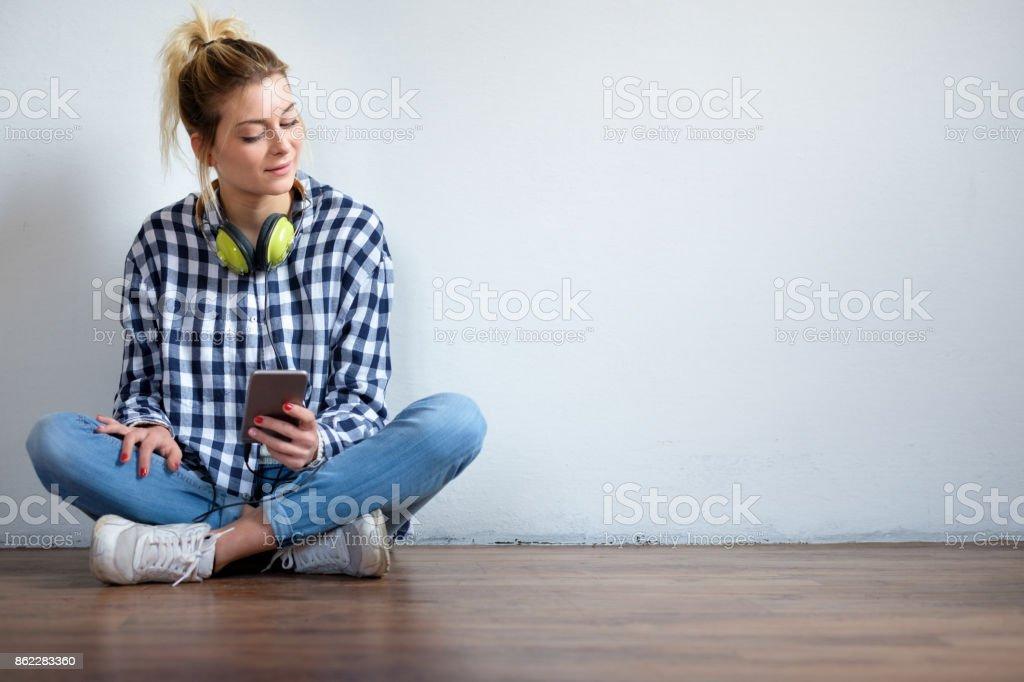 Chica sentada en el piso y con smartphone - foto de stock