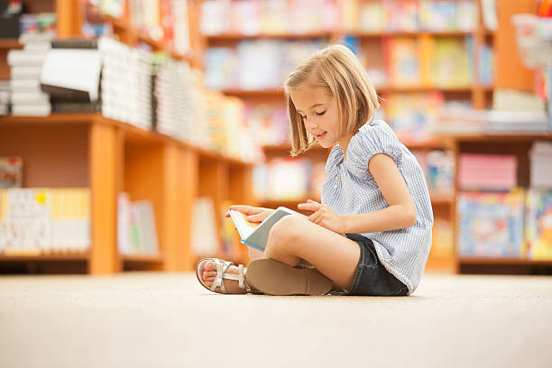 Girl sitting on floor of library with book stock photo