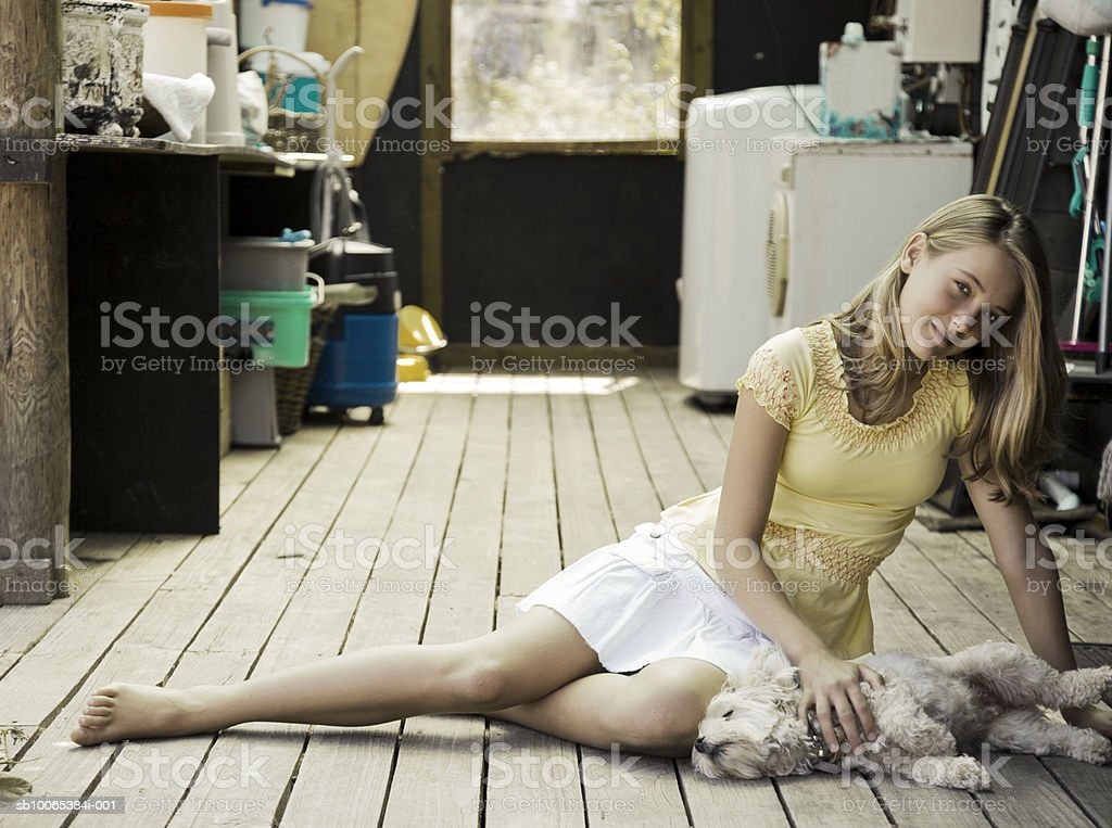 Girl (12-13) sitting on floor playing with dog, portrait royalty-free stock photo