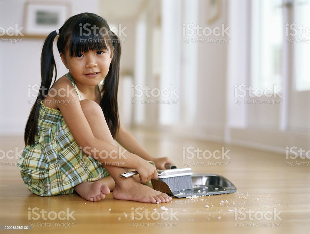 Girl (4-6) sitting on floor sweeping up crumbs into dust pan, portrait stock photo