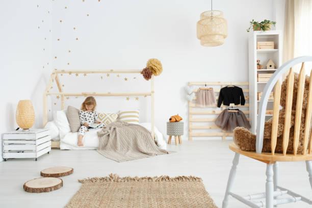 mädchen sitzen auf ihrem bett - schick moderne schlafzimmer stock-fotos und bilder