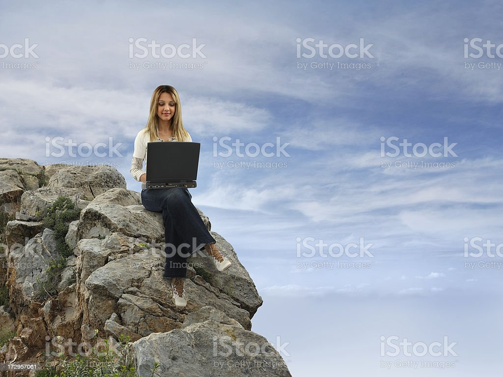 Girl Sitting On Hill A young girl sitting on hill top and using computer (laptop) with cloudy sky background. 20-29 Years Stock Photo