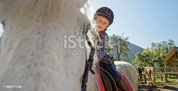 Girl sitting on horse on ranch.