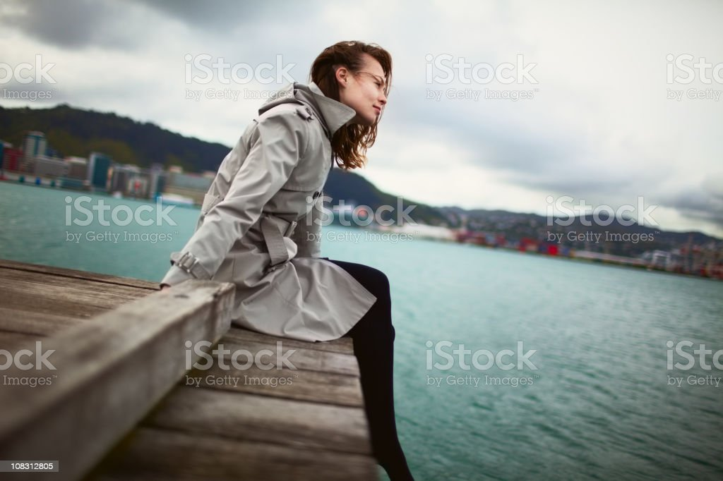 Girl sitting on jetty along royalty-free stock photo