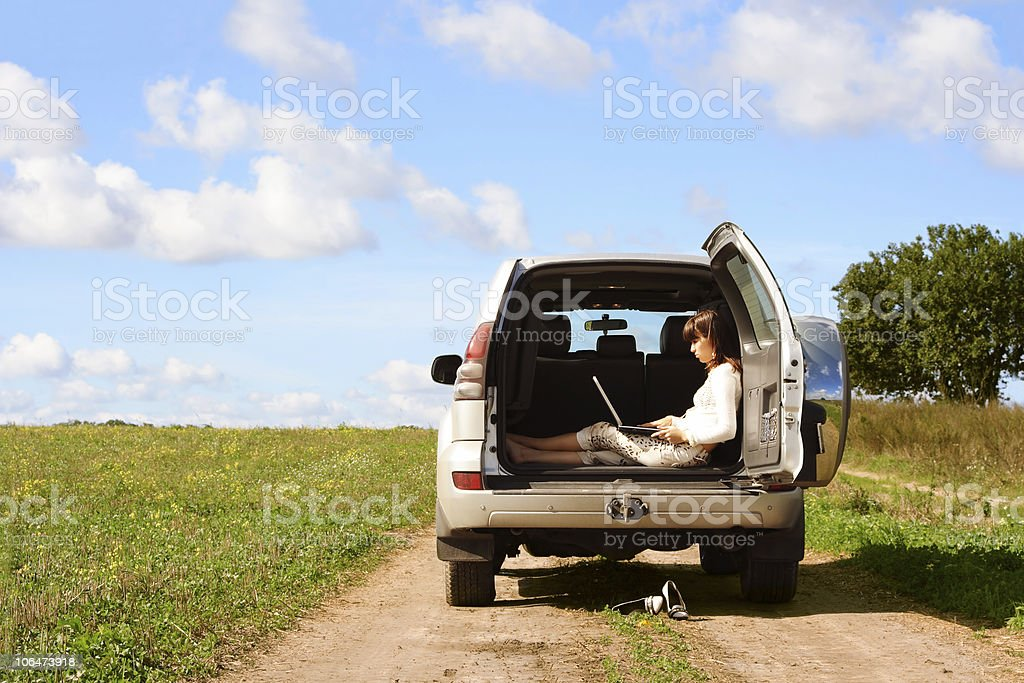 Girl sitting on laptop in back of 4x4 next to green paddock royalty-free stock photo