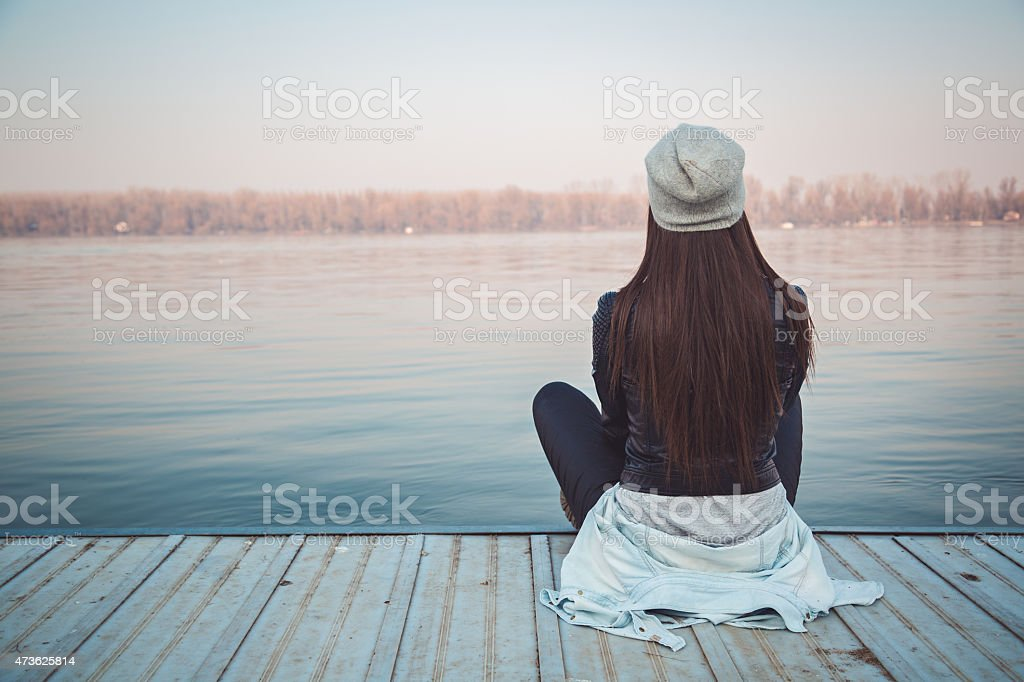 Girl sitting on pier and lookingat the river stock photo