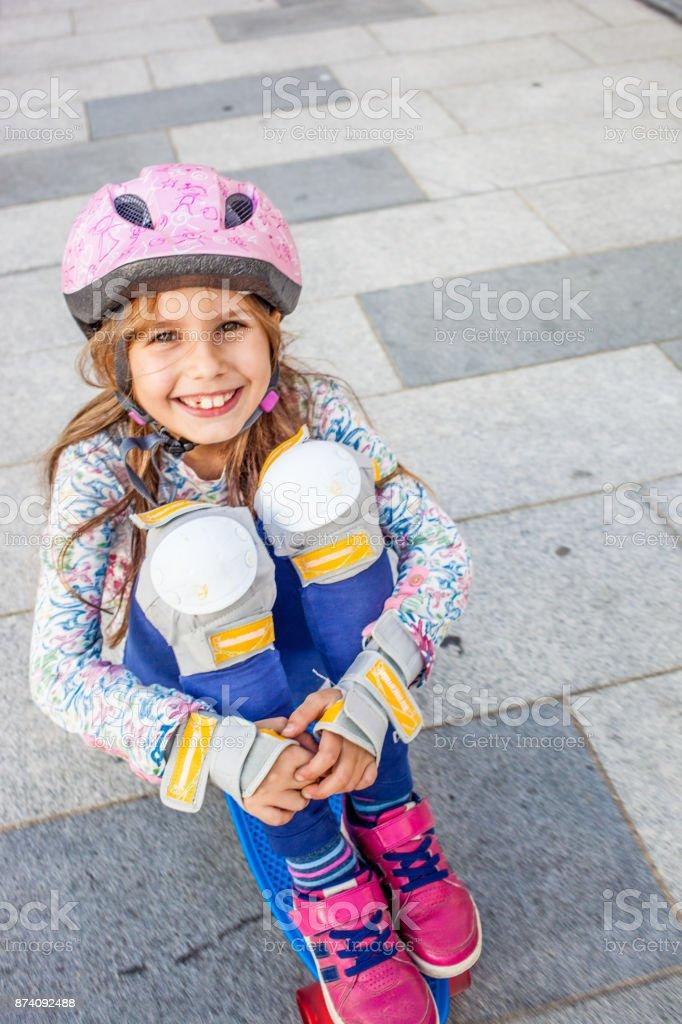 Girl Sitting on Skateboard stock photo