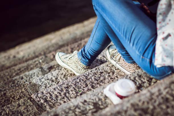 mädchen sitzen auf schritte detail - druck jeans stock-fotos und bilder