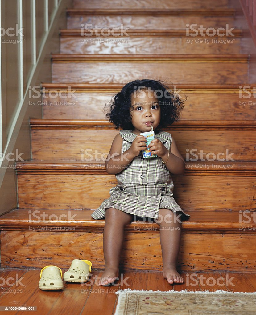 Girl (21-24 months) sitting on steps drinking, portrait royalty-free 스톡 사진