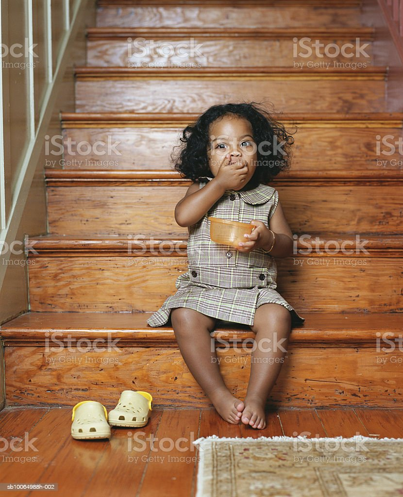 Girl (21-24 months) sitting on steps eating snacks, portrait foto de stock libre de derechos