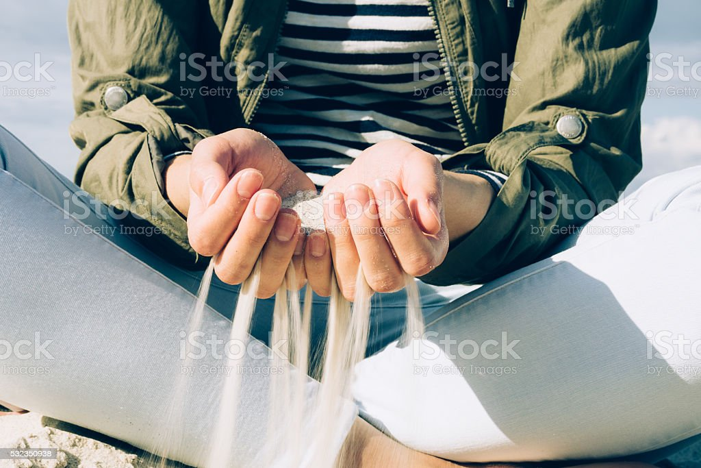 Girl sitting on the beach and keeps sand in palm stock photo
