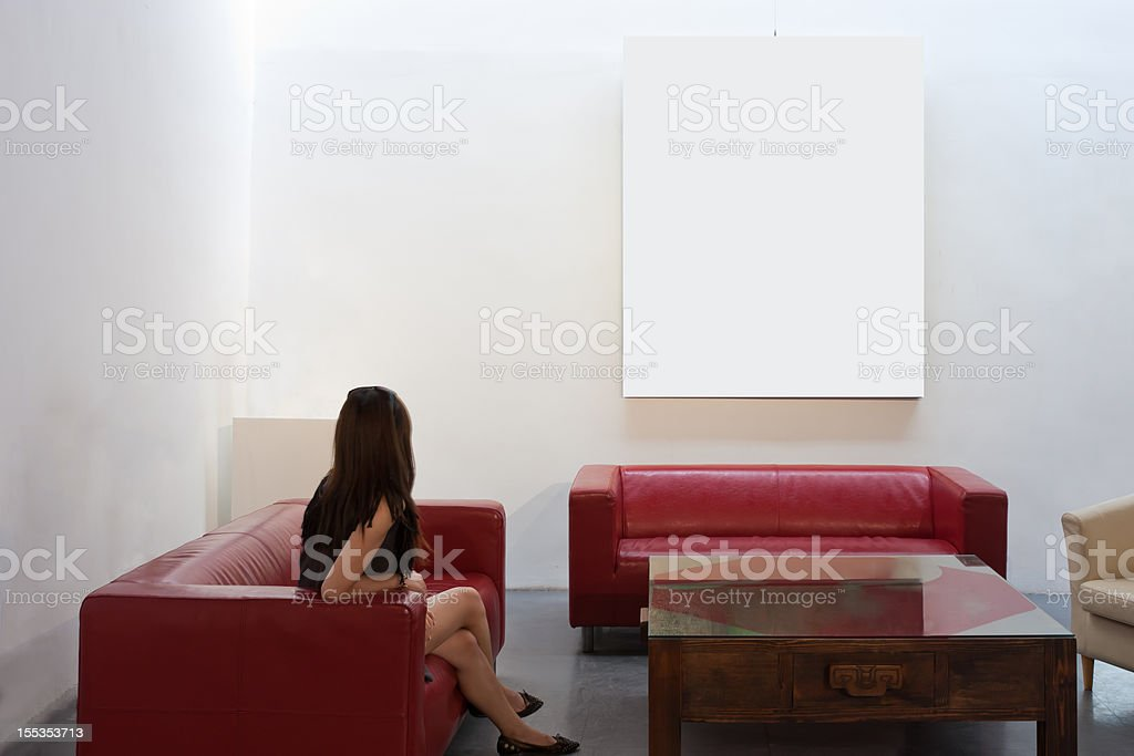 Girl sitting on the couch and watching frame royalty-free stock photo