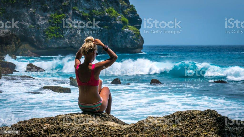 Girl sitting on the Rock and watching Huge Waves hitting Tembeling Coastline at Nusa Penida Island, Bali Indonesia royalty-free stock photo
