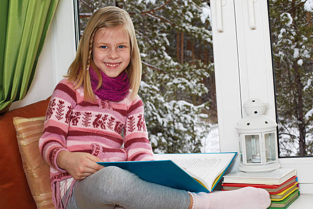 girl  sitting on the window on Christmas Eve stock photo