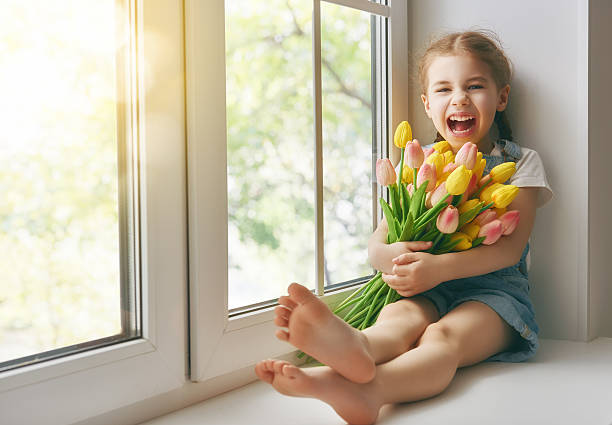 girl sitting on the window - house with flowers stock photos and pictures