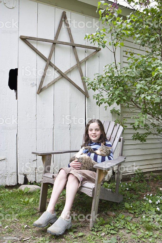 Girl sitting outside barn holding cat royalty-free stock photo