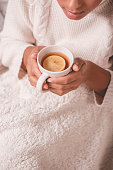 Girl with tea cup sitting under blanket