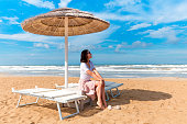 Girl sitting under sun umbrella on seashore. Rimini beach, Italy. Vacation background.