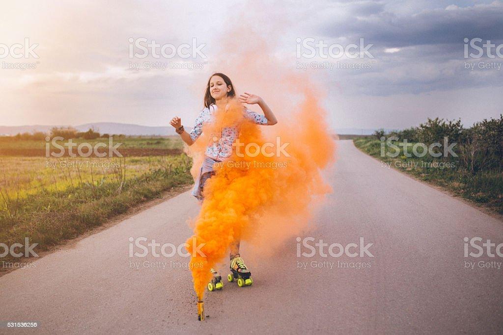 Chica patinaje rodeado de color naranja grenade de humo - foto de stock
