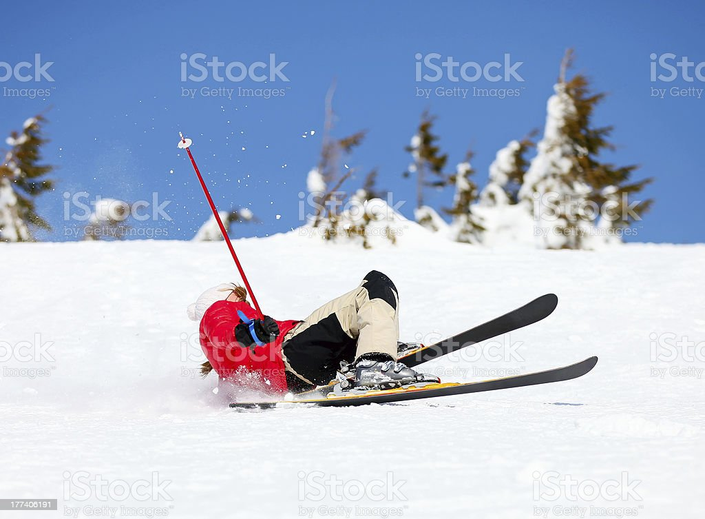 Girl skier falling down on mountain slope stock photo