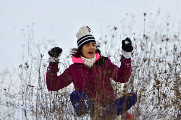 Girl sledding downhill on snow in winter and laughing with joy stock photo