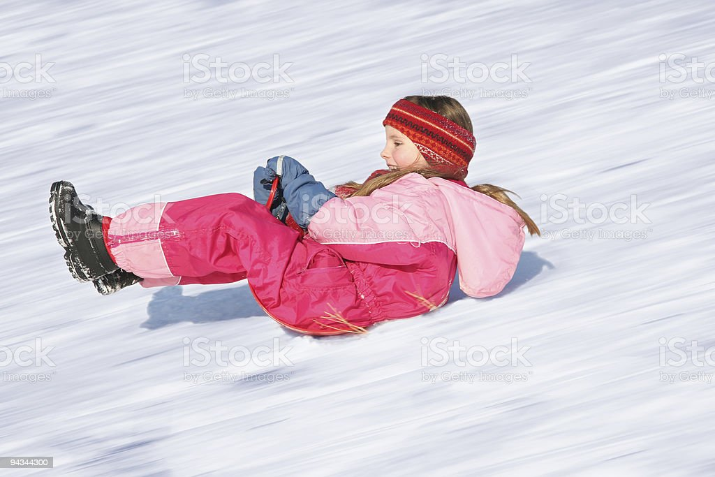 Girl sleeding down a snowy hill stock photo
