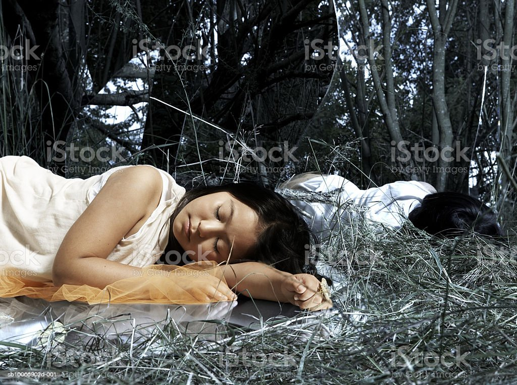 Girl (8-9) sleeping in grove, reflected in mirror royalty free stockfoto