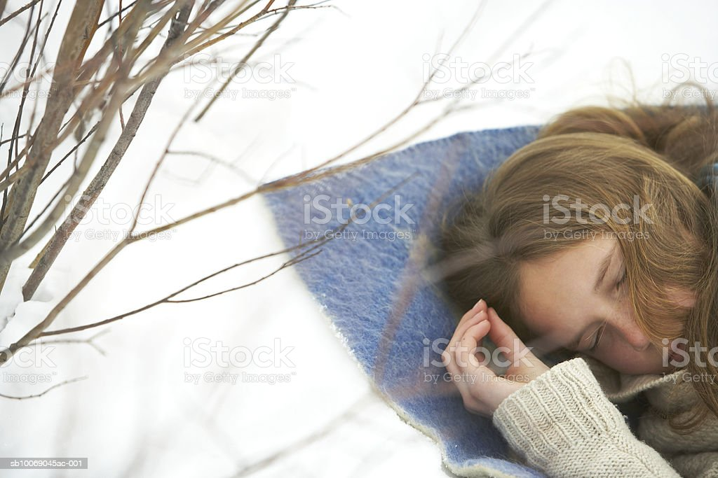 Girl (12-13) sleeping in snow royalty-free stock photo