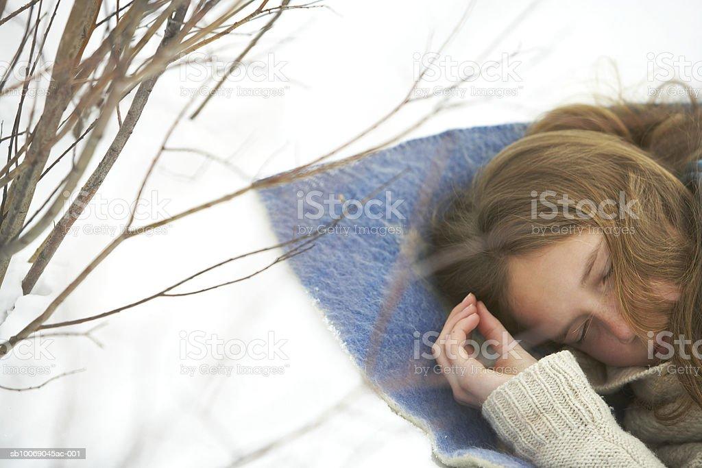Girl (12-13) dormir en la nieve foto de stock libre de derechos
