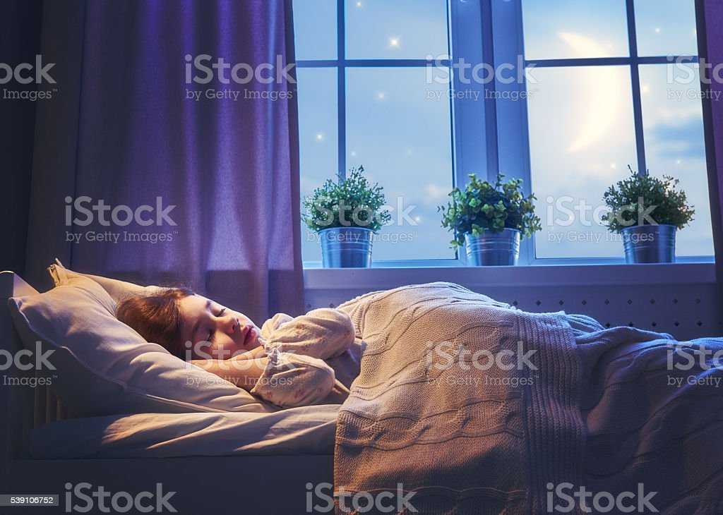 girl sleeping in the bed stock photo