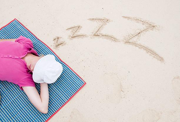 Girl sleeping on the beach stock photo
