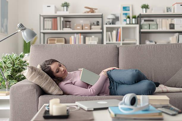 girl sleeping on the sofa - faire un somme photos et images de collection
