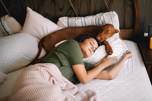 Girl sleeping with her dog.