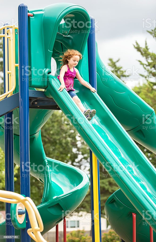 Girl Sliding Down Green Slide at Outdoor Playground stock photo