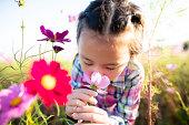 女の子は花園で花の香りを嗅ぎます
