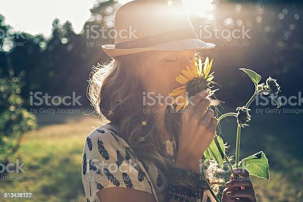 Photo of Girl smells sunflower