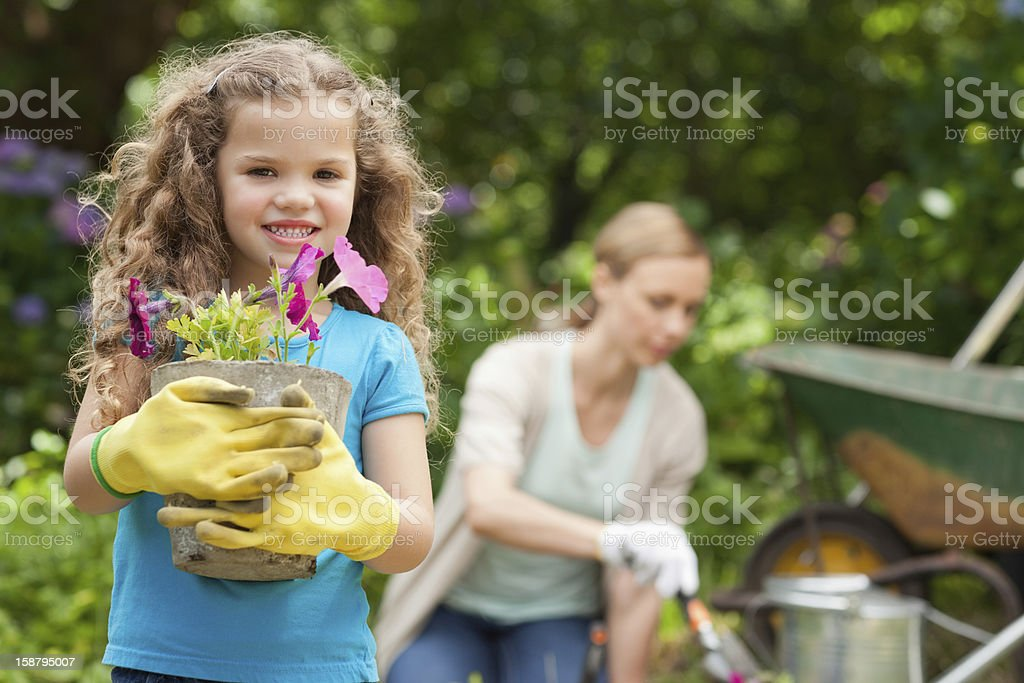 Girl smiling as she holds a flower while gardening royalty-free stock photo