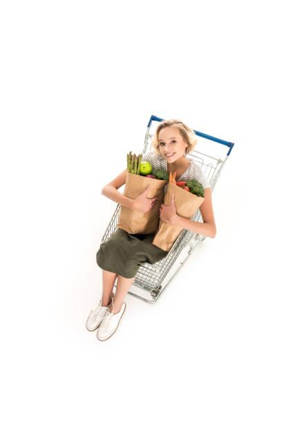mädchen lächelnd in die kamera halten sie einkaufstüten - trolley kaufen stock-fotos und bilder