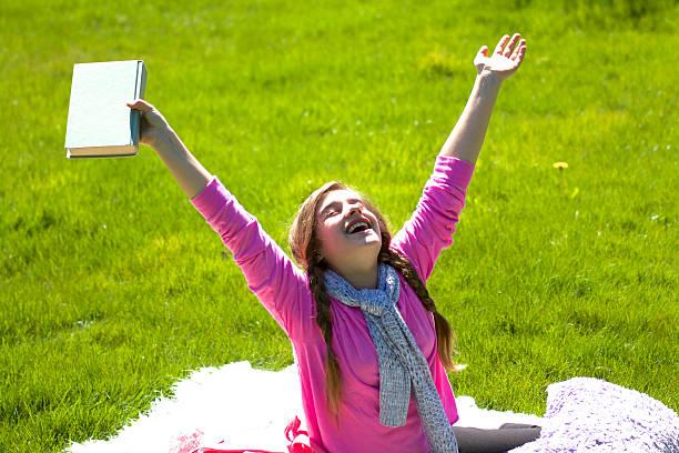 lächelndes mädchen lesen buchen ab - sommerfest kindergarten stock-fotos und bilder