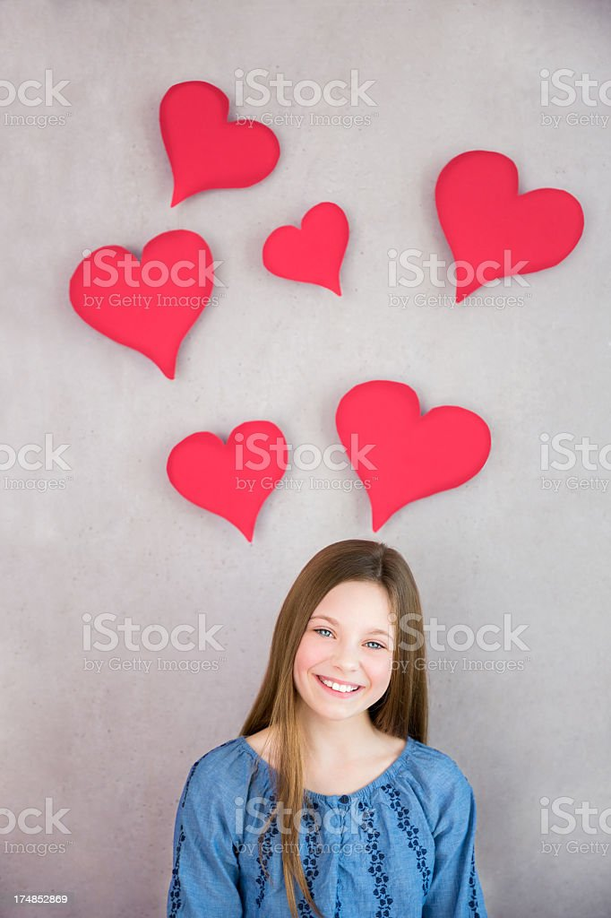 Girl smiling into camera with hearts above her head royalty-free stock photo