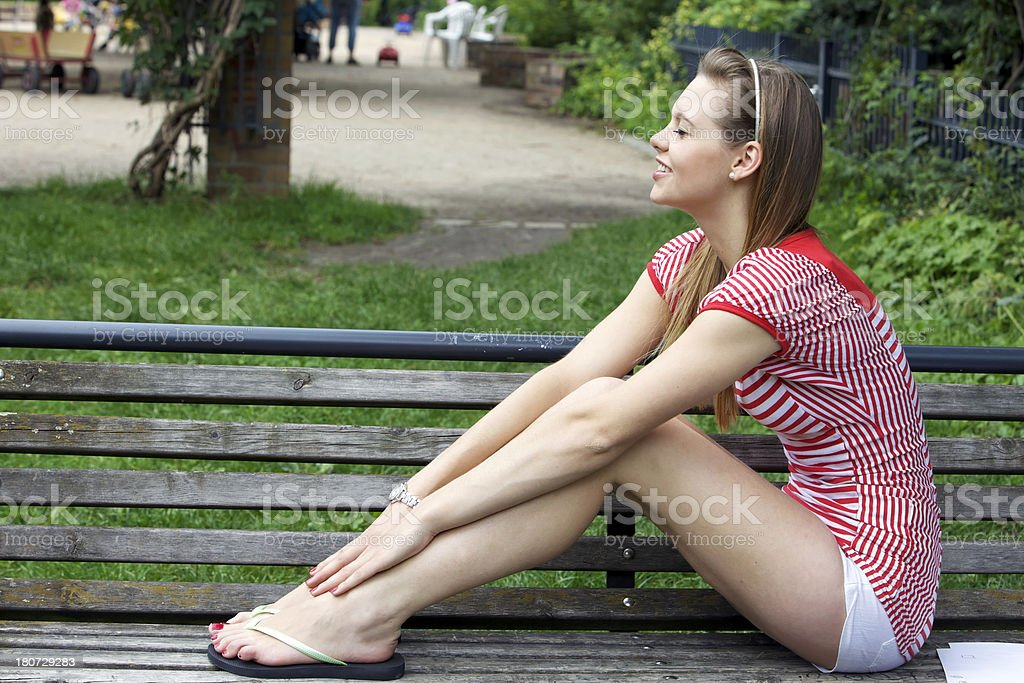 Girl Smiling Outside on Park Bench royalty-free stock photo