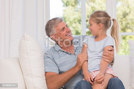 Grandfather and granddaughter sitting together on sofa. Portrait of an old senior man talking to little girl. Granddaughter sitting on grandfather legs and talking.