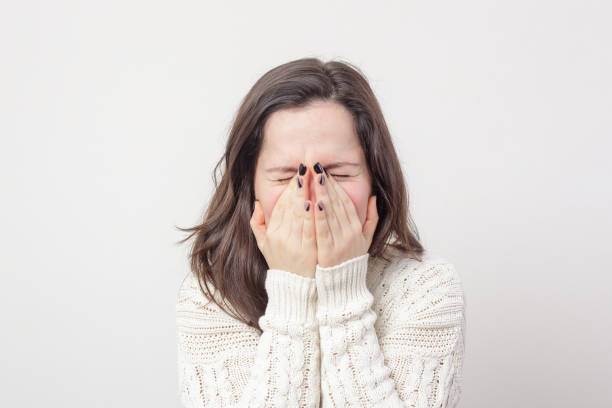 Girl sneezes, covering her face stock photo