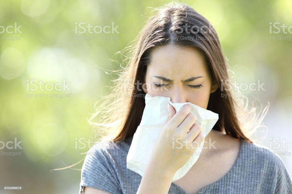 Chica estornudos y soplar en un trapo - foto de stock