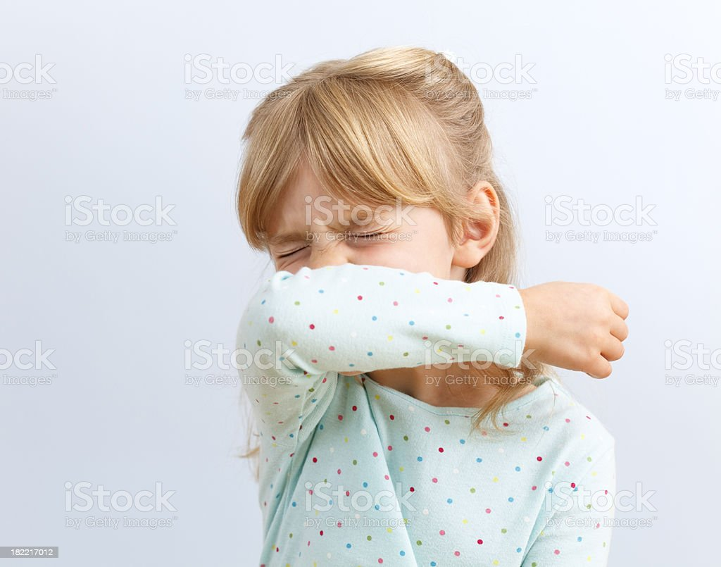 Girl sneezing into crook of arm royalty-free stock photo