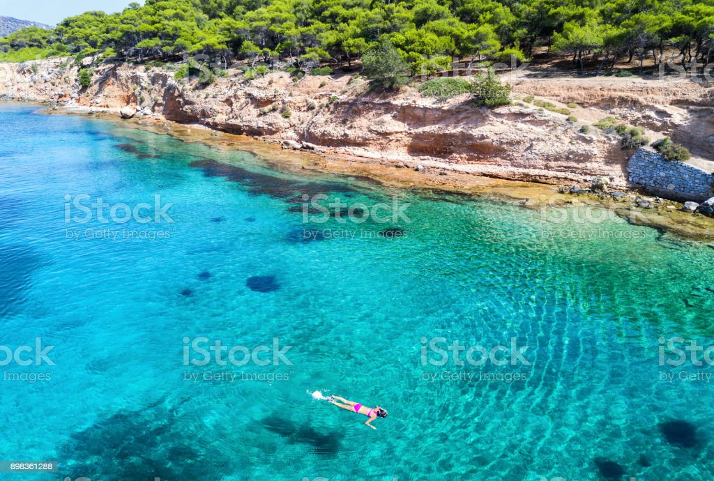 Girl snorkeling in the turquoise waters of Moni Island stock photo